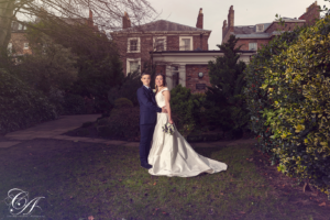 Bride and groom stood in the gardens of the York Register Office with the building in the background. York Wedding Photography
