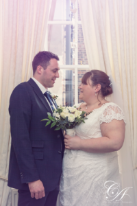 Bride and groom stood in the window looking at each other at the York Registry Office.