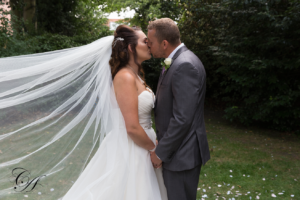 Bride and groom kissing in the gradens or the York Registry Office gardens