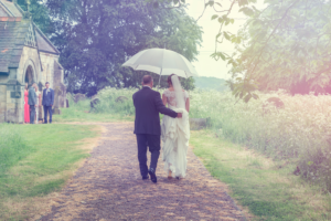 Bride and father walking to All Saints Church in the rain at Moor Monkton, York. Wedding Photography by Charlotte Atkinson