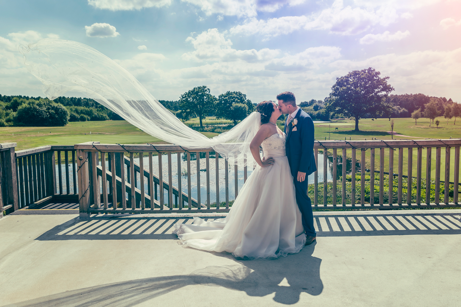 Bride and groom stood on the balcony at Sandburn Hall in York, with the vail blowing in the wind. Wedding Photography by Charlotte Atkinson