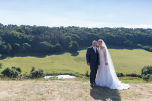 Couple stood together, with the stunning view in the background from Stepney Hill Farm wedding venue