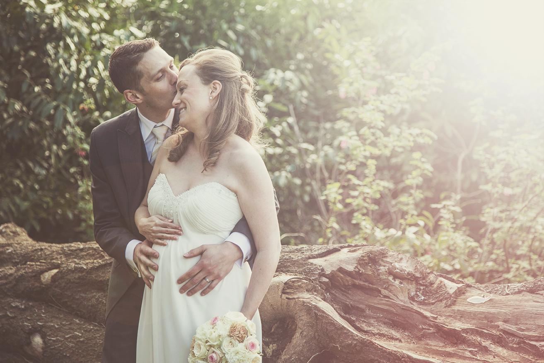 Groom kissing bride on her head