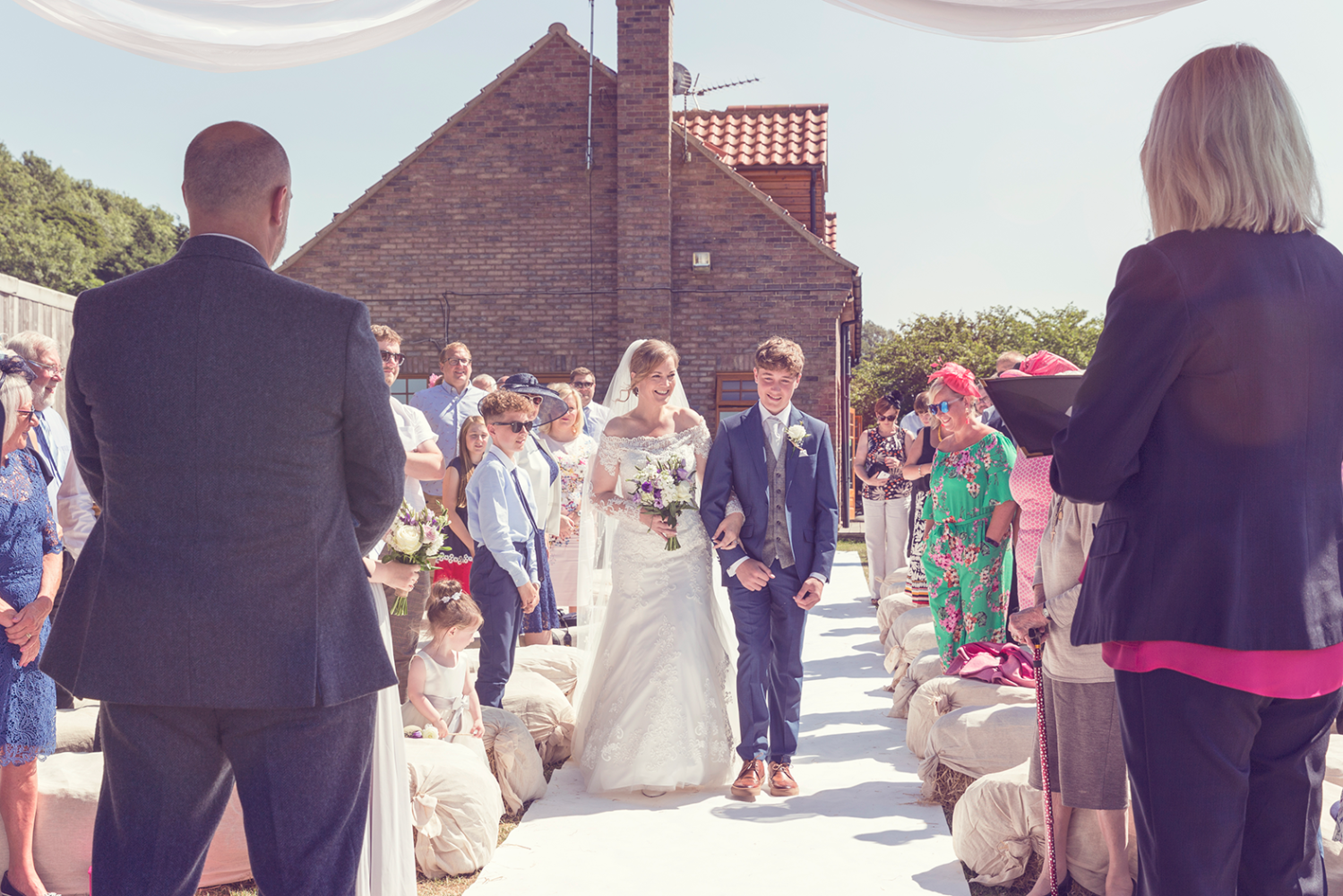 Bride walking down the aisle with her son at Stepney Hill Farm Wedding Venue