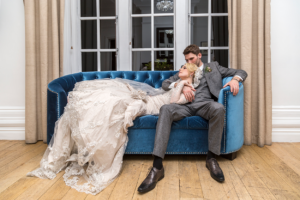 Groom sat on a blue sofa with the bride laid over him, at Woodlands Hotel in Leeds. Wedding Photography by Charlotte Atkinson Photography