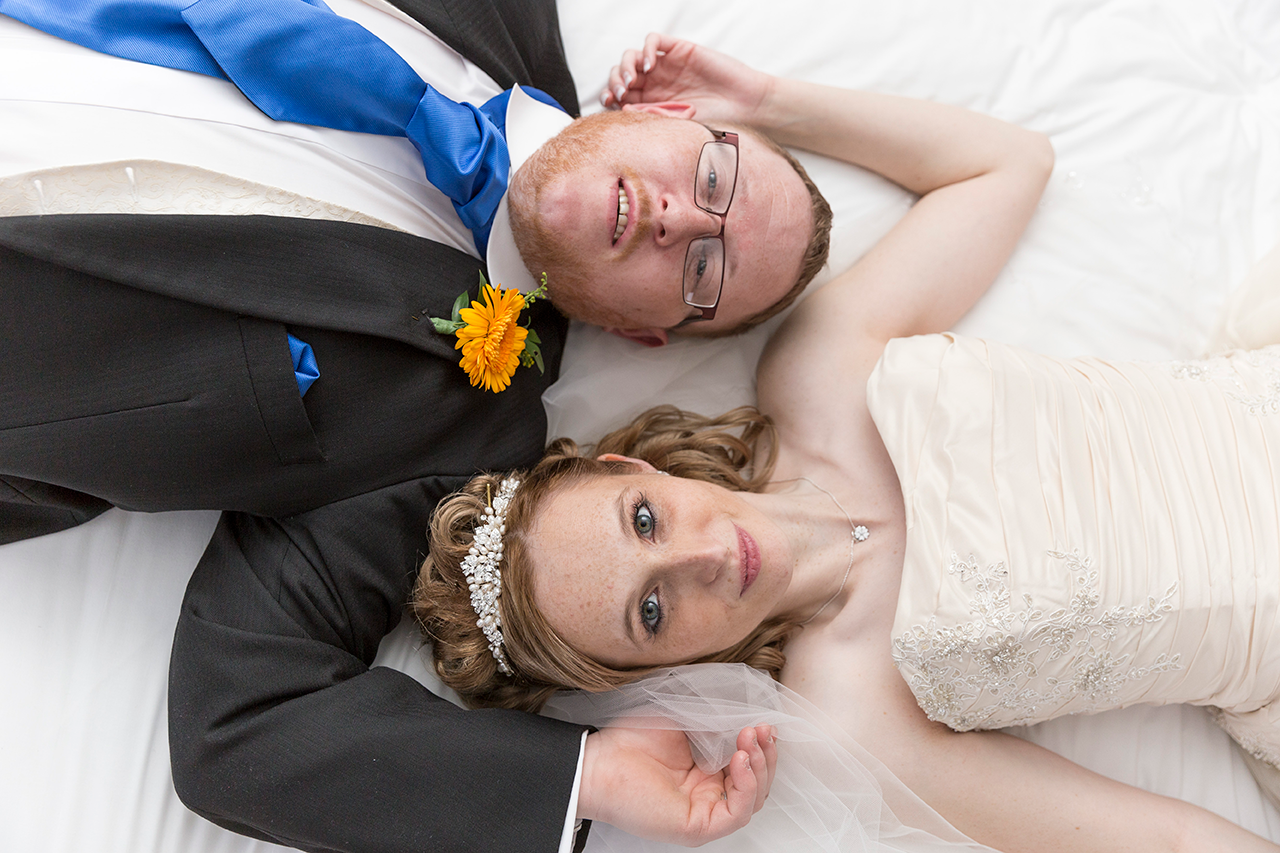 Bride and Groom laid on the bed looking up