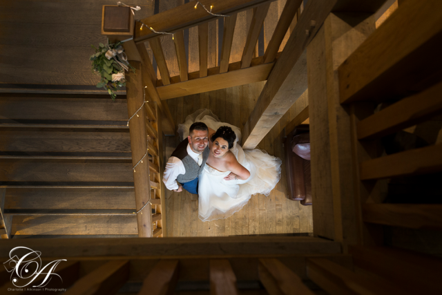 Bride and groom stood looking up to the York Wedding Photographer, who is taking the photo from the top of the stairs at Sandburn Hall, York.