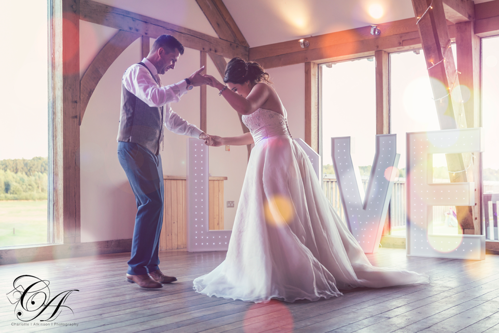 Bride and groom having their first dance, with a LOVE sign in the background. York Wedding Photographer at Sandburn Hall.