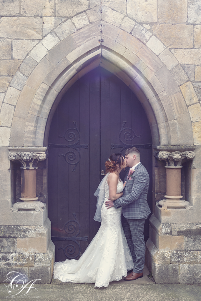 Bride and groom stood in front of the church door kissing at their York Wedding
