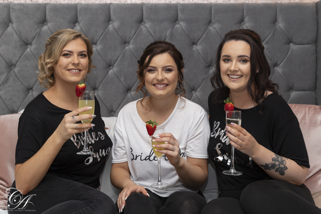 Bride and her bridesmaids sat on the bed with drinks, ready for their York Wedding