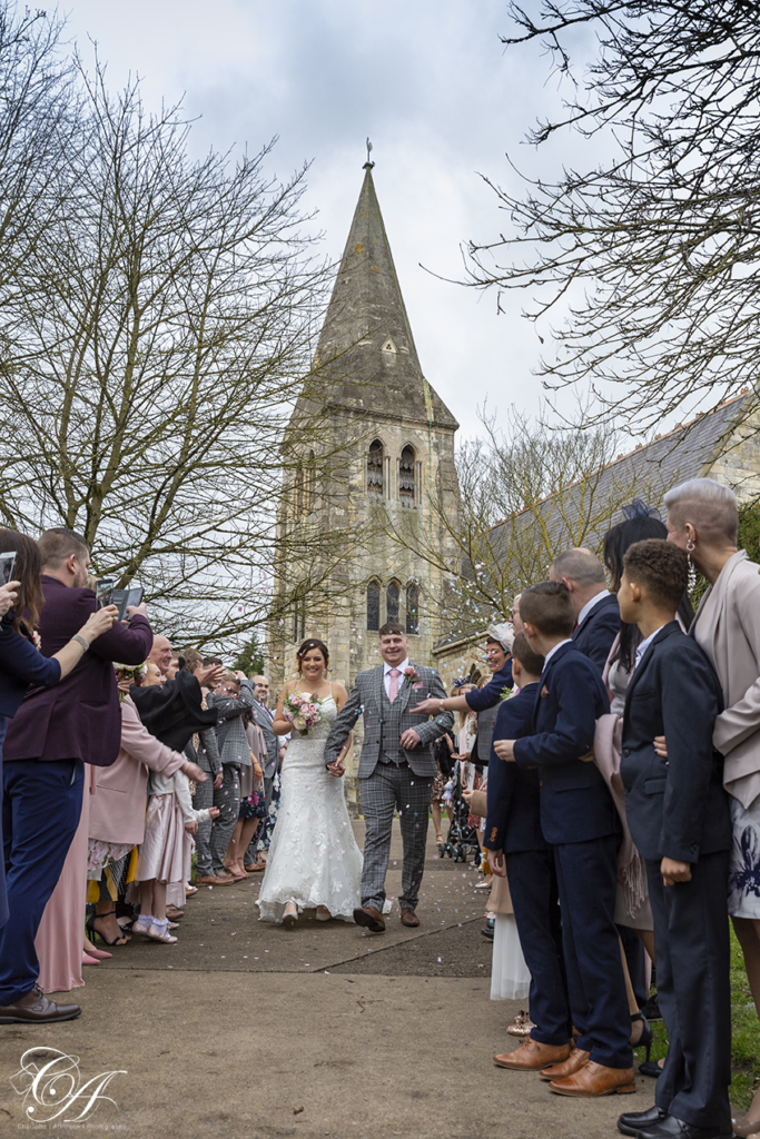 Bride and groom walking away from the church while their guests throw confetti at their York Wedding