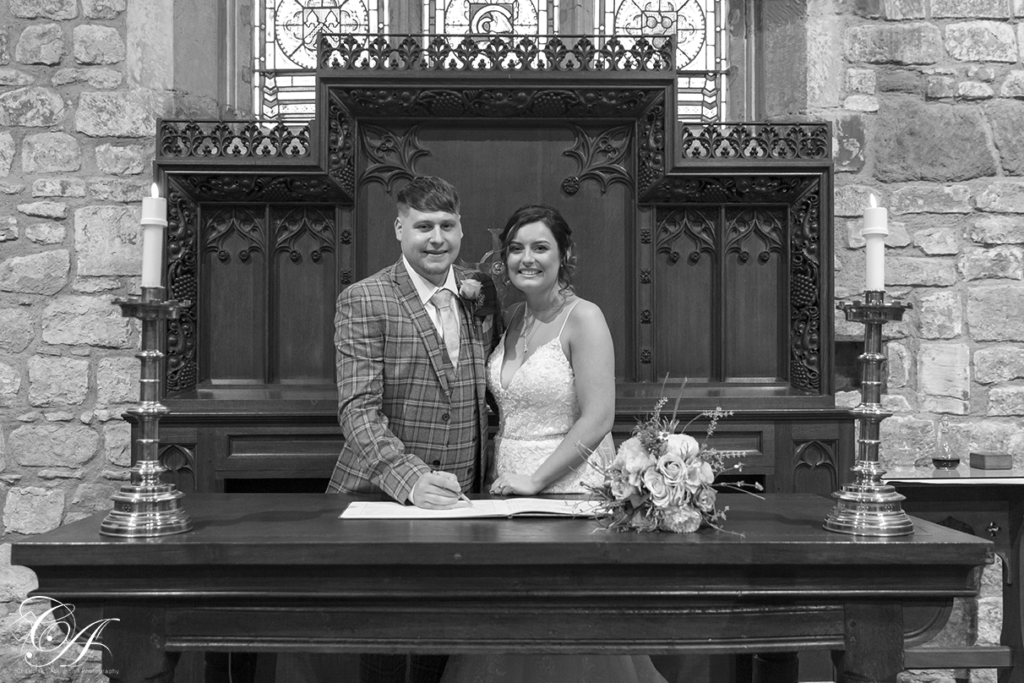 Bride and groom signing the register at their York Wedding