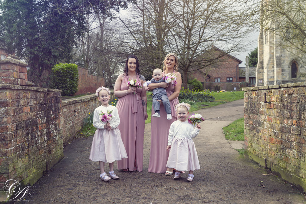 Paige boy, bridesmaids and flower girls stood in enterance to the church grounds. York Wedding