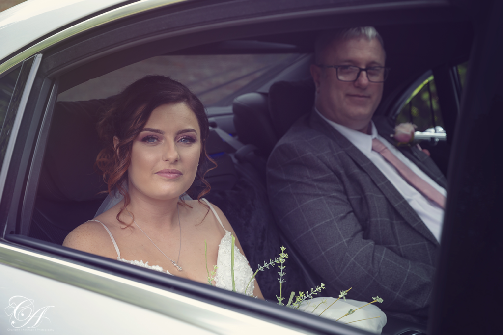 Bride and father sat in the car looking through the car window. York Wedding