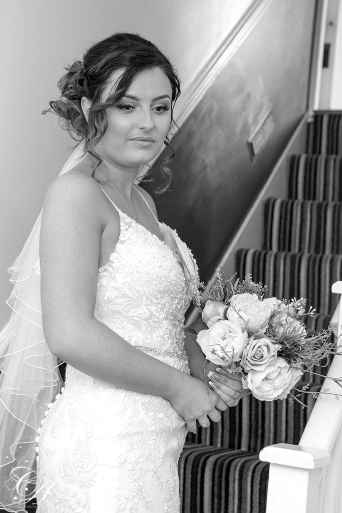 Bride gazing in to the distance, on the stairs. York Wedding