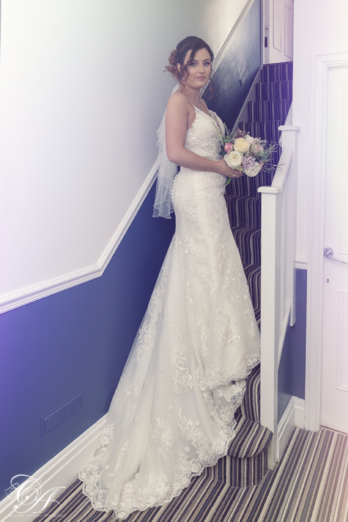 Bride stood with her flowers on the stiars and the dress trailing behind. York Wedding