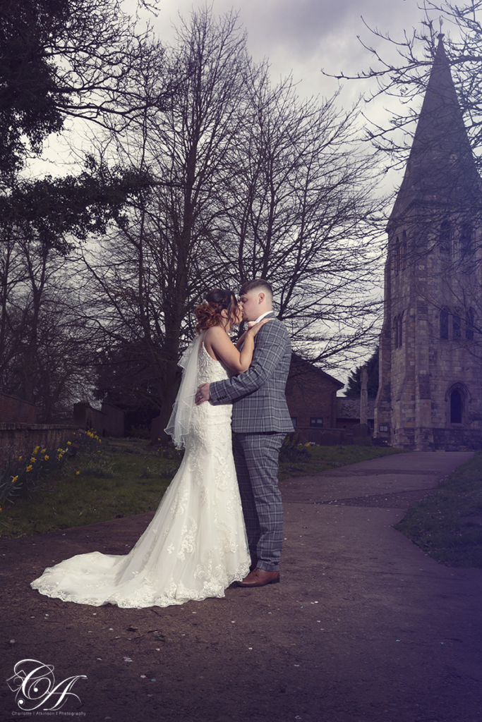 Bride and groom kissing in front of the church. York Wedding