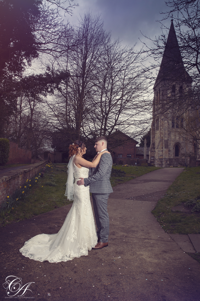 Bride and groom stood face to face in front of the church. York Wedding