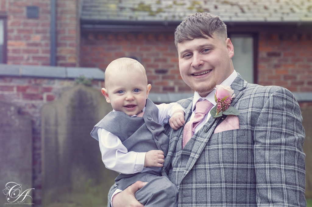 Groom and holding his son in his arms in the church grounds of their York Wedding.