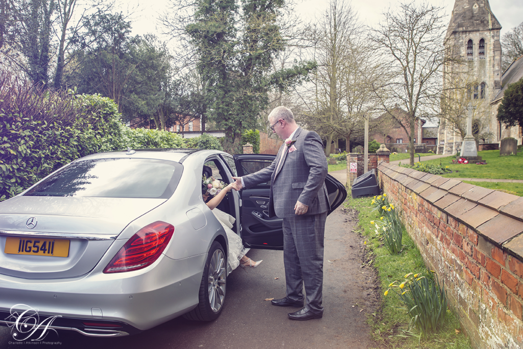 Father helping his daughter to get out of the car. York Wedding