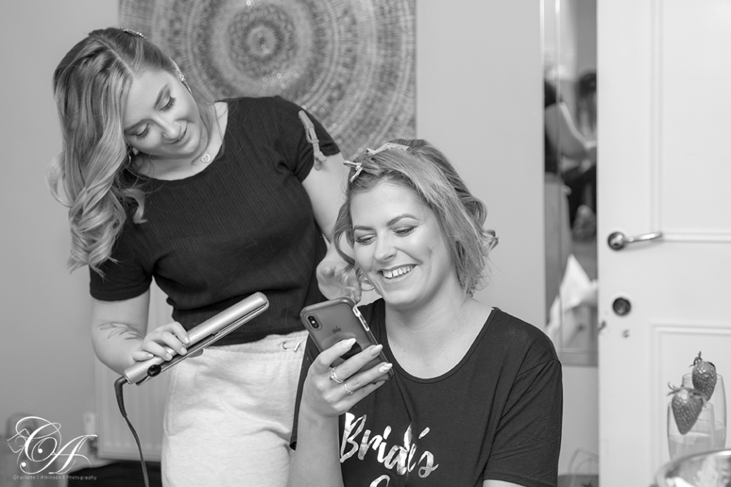 Bridesmaid getting her hair styled while on her phone. York Wedding