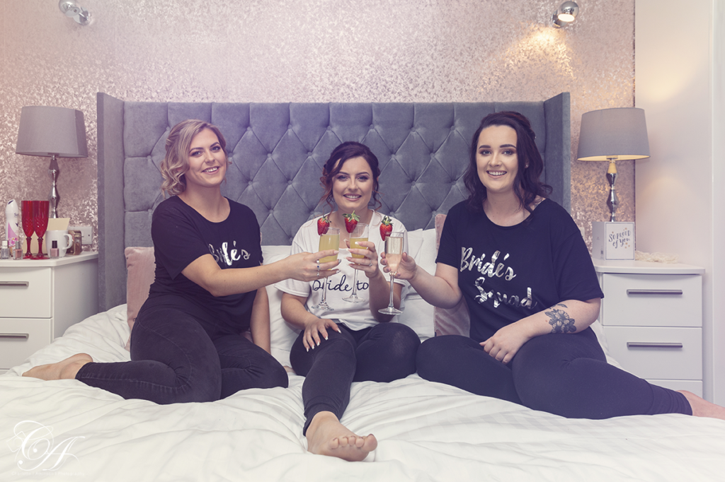 Bridal Prep, bride and bridesmaids sat on the bed with drinks. York Wedding