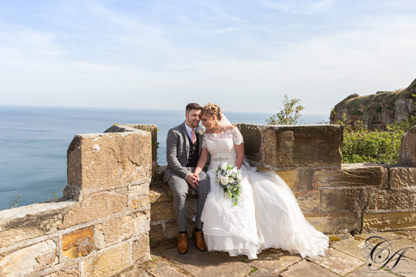 Bride and groom sat on the wall at Raven Hall Hotel. Scarborough Wedding Photographers