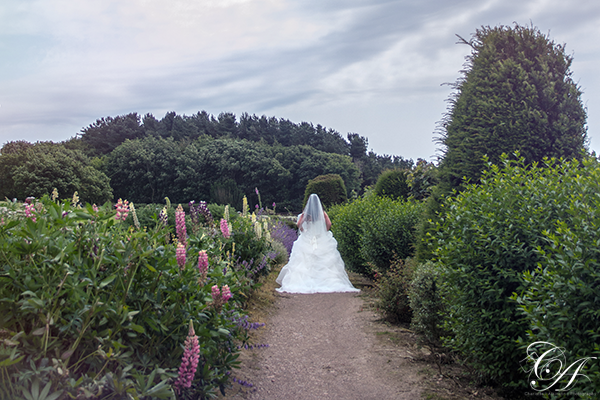 Bride walking through the flowers at Raven Hall Hotel, Scarborough Wedding Photographer